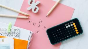 Afbeelding van een rekenmachine op papier met pennen en getallen